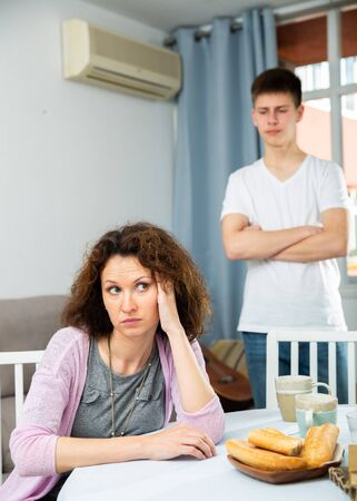 Portrait of offended mother after disagreements with teenager son sitting at home 版權商用圖片