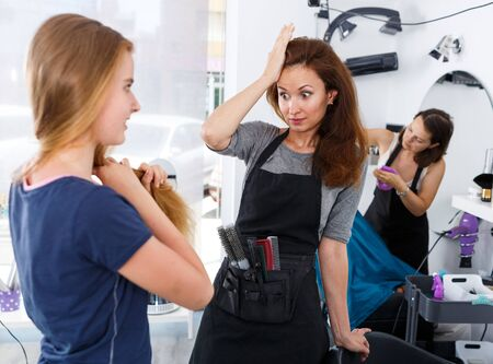 Puzzled young hairstylist inspecting hair of teen girl before haircut in hair salon