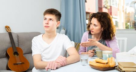 Portrait of troubled teen boy and his mother scolding him in home interior