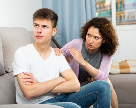Annoyed mother discussing misbehavior with teenage son at home