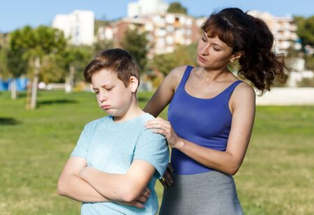 Frustrated boy standing while mother berating him outdoors