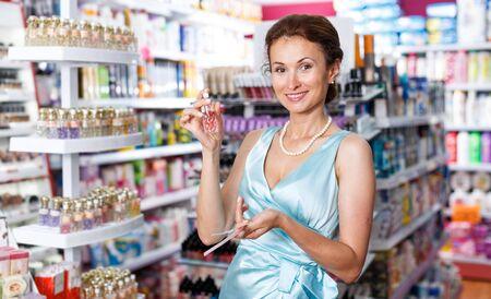 Stilvolle weibliche riechende Parfümtester, die Parfüm im Laden wählen Standard-Bild