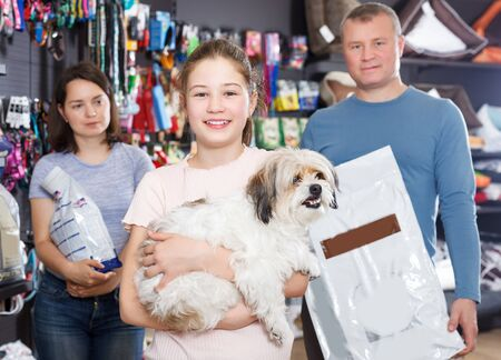 happy preteen girl with havanese pup while shopping with parents in pet store