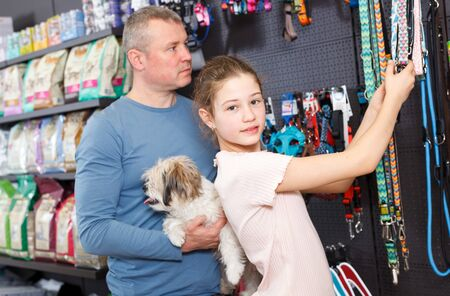 Happy little girl with her father visiting pet shop in search of accessories for their dog