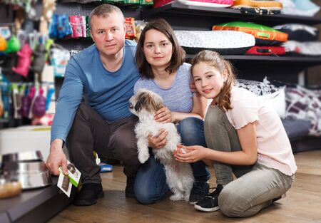 smiling young family with little dog in store of pet accessories Фото со стока