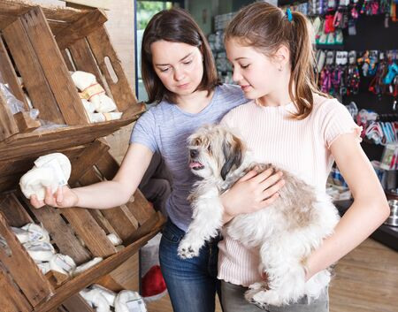 happy preteen girl with young mother visiting pet shop in search of treats for their dog