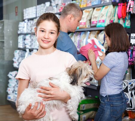 Portrait of happy cheerful glad cute girl with her little dog visiting pet supplies shop with parents