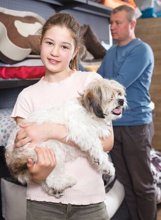 Portrait of cheerful preteen girl with havanese pup while shopping with parents in pet store