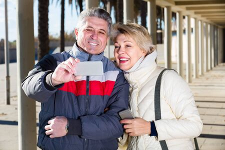 Cheerful mature married couple walking near the columns and make selfie