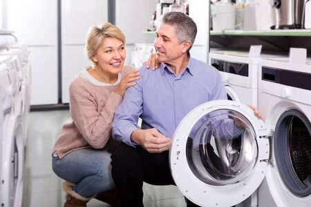 Mature couple choosing modern washing machine in appliances store Stock Photo