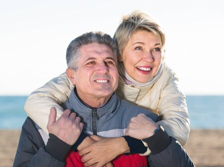 husband and wife spend time together happily at sea beach on bright day