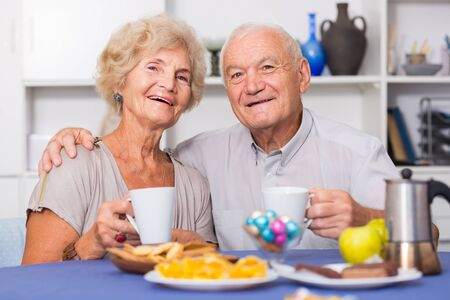 Smiling elderly spouses enjoying time at home, drinking tea with sweets
