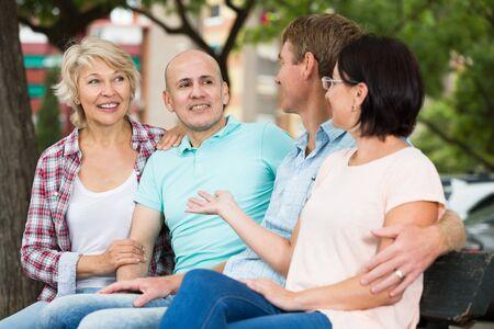 Vriendelijke en blije gepensioneerden die in het weekend in het park praten