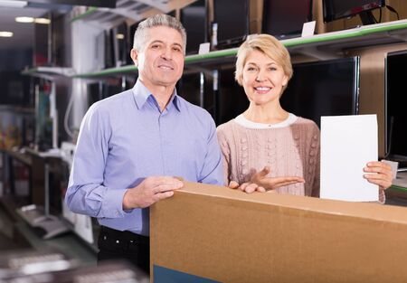 Lovely mature married couple are happy buying on credit household appliances for home