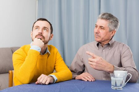 Mature father and son is serious conversation at table at home