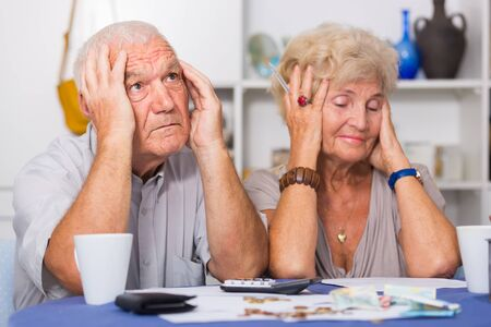 Upset retired couple calculating domestic finances with calculator and bills on table Фото со стока