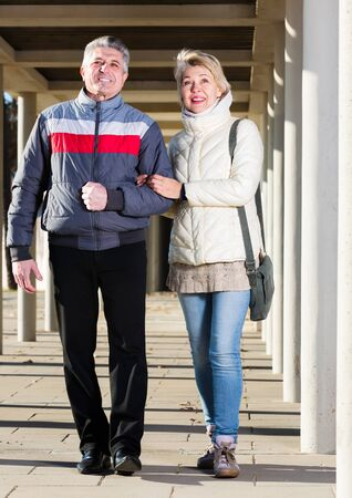 Mature husband and wife are walking together clear sunny day between columns Stock Photo