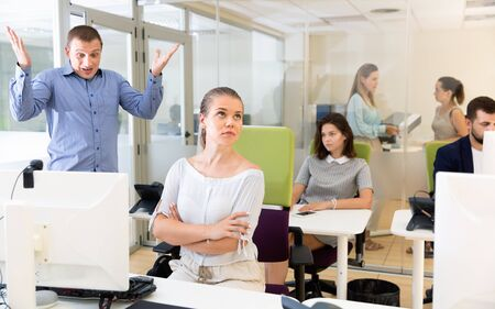Chica molesta sentada en la computadora portátil en el espacio de coworking mientras el empresario enojado infeliz insatisfecho señala errores en su trabajo