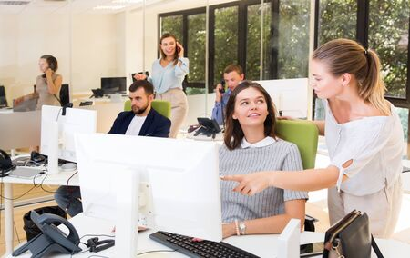 girl helping happy female colleague in work with computer in modern coworking space