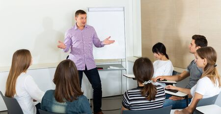 Male manager making presentation on staff meeting in office