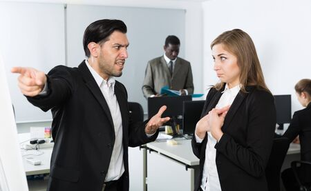 Angry male boss pointinting to misses in work to woman  manager working in office