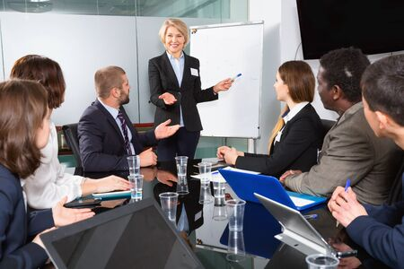 Elegant cheerful  glad mature businesswoman discussing new project with his team in meeting room