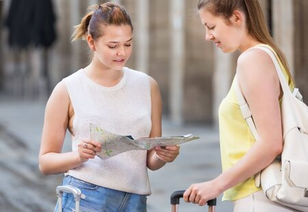 Young happy two sisters searching on their paper map and route in a town Stock Photo