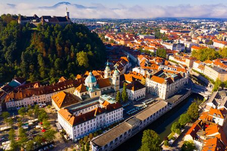 View from drone of historical center of Slovenian city of Ljubljana with medieval castle on Castle Hill in autumn morning