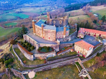 Aerial view of ancient fortified castle of Chateau de Bouzols in cloudy winter day, Arsac-en-Velay, France Redactioneel