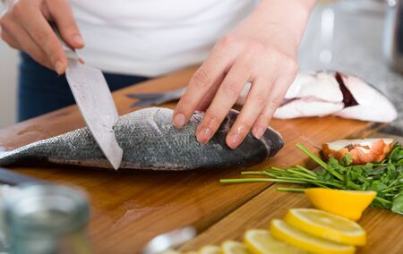 Close up image female hands cooking dorado fish on cutting board 写真素材