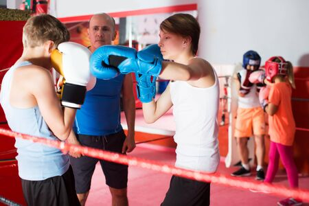 Group of kids exercising with coach on boxing ring at gym