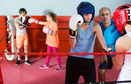 Group of children exercising with coach on boxing ring at gym