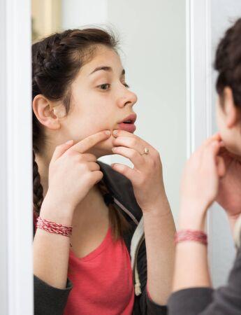Jonge tiener schoonmakende gezichtshuid alleen thuis