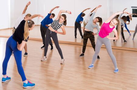 happy european teenage boys and girls with trainer stretching in dance hall