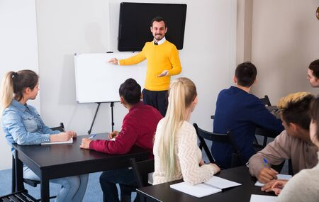 Giovani ragazze e ragazzi stanno lavorando in grandi gruppi a scuola.