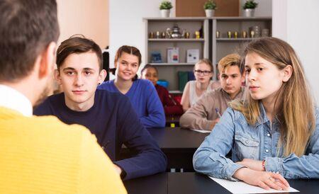 Estudiantes masculinos y femeninos serios siguiendo las explicaciones del maestro en clase