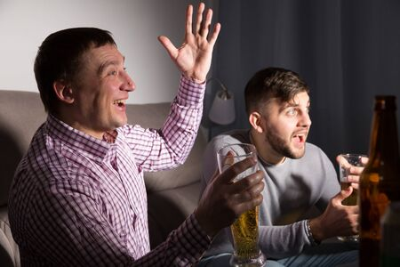 Two male friends watching football match on tv at home and having fun together