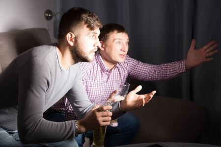 Worried concentrated men watching sporting match drinking beer at home Zdjęcie Seryjne