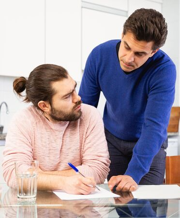 Man having problems with some documents; worriedly discussing with friend at home table Stock Photo