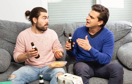 Men drink beer and watch the match on TV