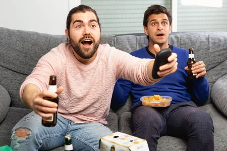 Two men watching matchup on tv with shouts of joy while drinking beer together at home Zdjęcie Seryjne