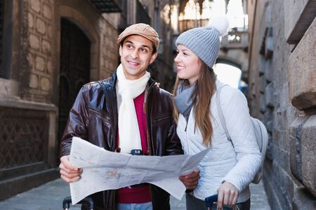 Positive smiling man and woman with map and package looking attraction outdoors 免版税图像
