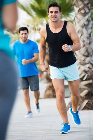 Smiling sportsmen are joggning race in time warm-up in the park near beach. 스톡 콘텐츠