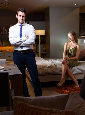 Elegant man in white shirt and tie standing near table in room while young attractive woman sitting on bed behind him Stock Photo