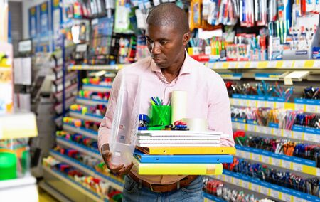 Glad cheerful positive African American man choosing office supplies at stationery department of supermarket