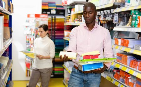 Portrait of glad  positive male and female customers choosing stationery at store Stock Photo