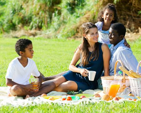 Smiling young parents with happy preteen daughter and son having fun together at picnic in summer city park