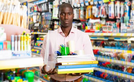 Portrait of friendly African man choosing stationery at shop 版權商用圖片