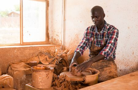 Concentrated African craftsman enjoying work with clay on potter wheel, making ceramic dishes Stock Photo