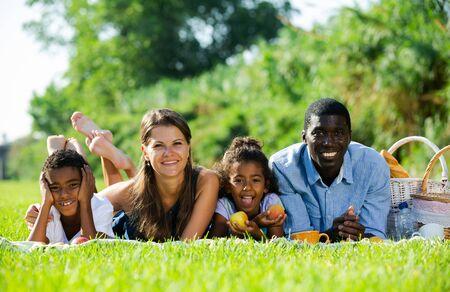 Porträt einer glücklichen interracial-Familie mit zwei Kindern, die auf einer Decke auf der grünen Wiese liegen und ein Picknick genießen Standard-Bild